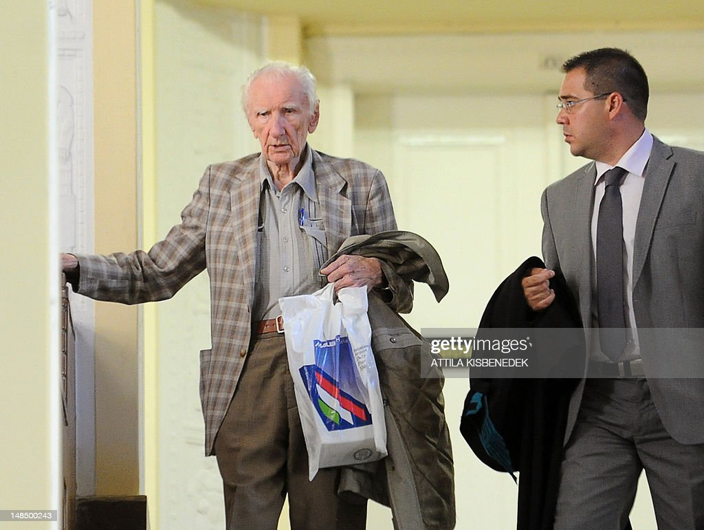 Laszlo Csatary (L), aka Ladislaus Csizsik-Csatary, leaves the courthouse in Budapest on July 18, 2012, with his Hungarian appointed lawyer Gabor Horvath (R), after he was placed under house arrest for 30 days following questioning by an investigative judge at the military's prosecution's office. Meanwhile the Simon Wiesenthal Centre welcomed the arrest by Hungarian police of the Nazi war crimes suspect, who topped the US Nazi-hunting organisation's most wanted list. Csatary is accused by the Wiesenthal Center of having helped organise the deportation of some 15,700 Jews to the Auschwitz death camp during World War II. AFP PHOTO / ATTILA KISBENEDEK