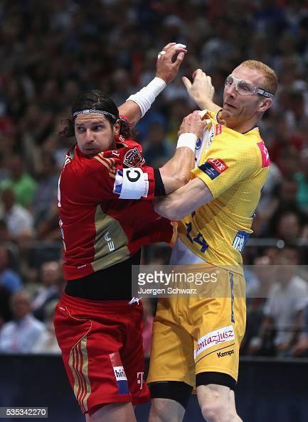 Laszlo Nagy of Veszprem blocks Mateusz Jachlewski of Kielce during the EHF Champions League Final between KS Vive Tauron Kielce and MKB Veszprem on...