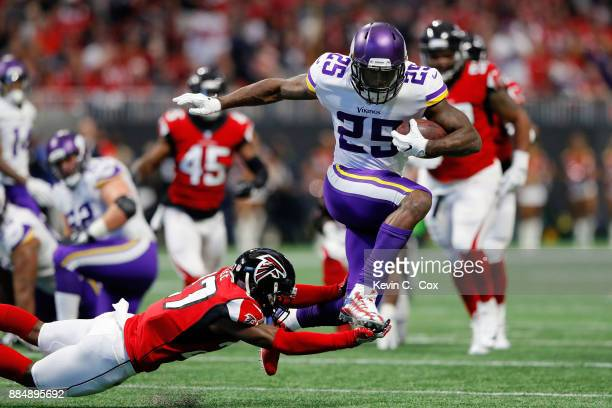 Latavius Murray of the Minnesota Vikings avoids the tackle by Damontae Kazee of the Atlanta Falcons on a long run during the first half at...