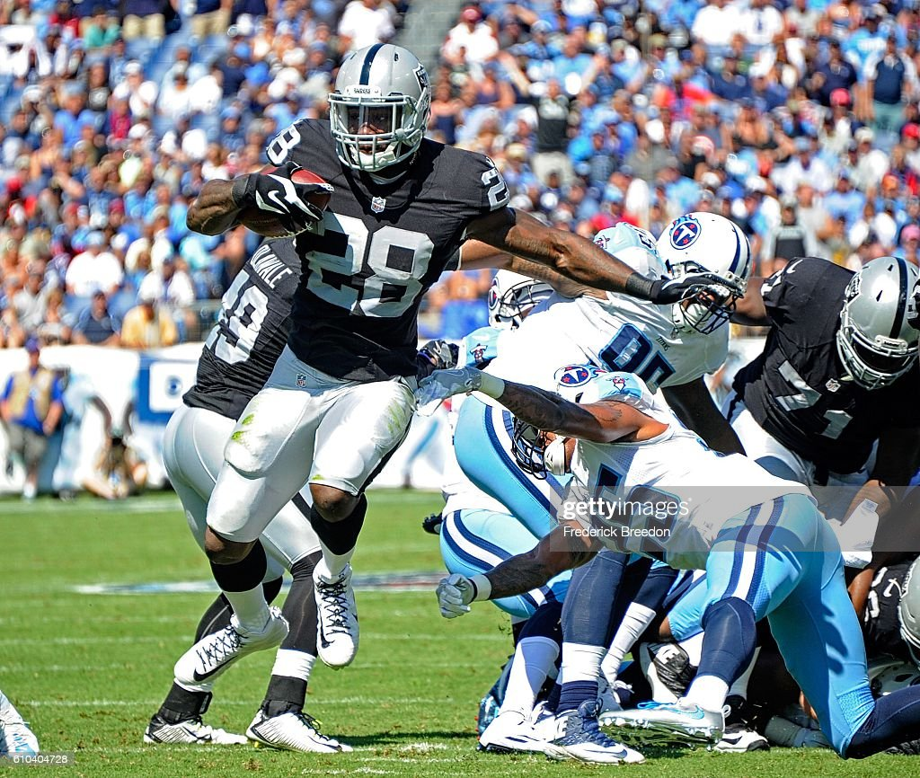 Latavius Murray #28 of the Oakland Raiders breaks a tackle from Rashad Johnson #25 of the Tennessee Titans opening him up to score a touchdown during the first half at Nissan Stadium on September 25, 2016 in Nashville, Tennessee.