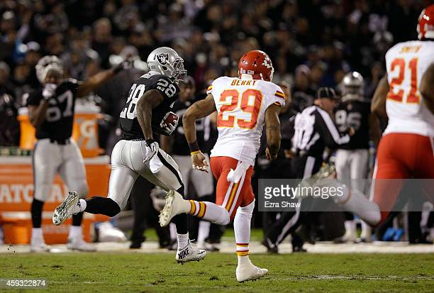 Latavius Murray of the Oakland Raiders runs the ball for a touchdown as Eric Berry of the Kansas City Chiefs pursues in the second quarter of the...