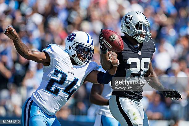 Latavius Murray of the Oakland Raiders runs the ball up the middle for a touchdown and has it knocked out of his hands by Daimion Stafford of the...
