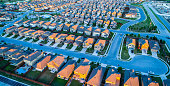 Aerial Drone View above Modern Development Suburbia , Rows after Rows , Thousands of Homes and Rooftops , Afternoon Sunset on Modern Suburban Neighborhood Community North Austin Texas The Suburbs