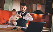 Single businessman father checking the time while holding baby boy in the kitchen
