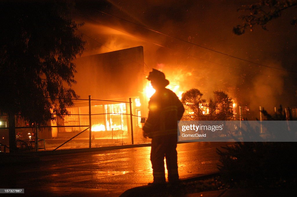 Late Night Fire with Fireman Silhoutted Against Flames : Stock Photo