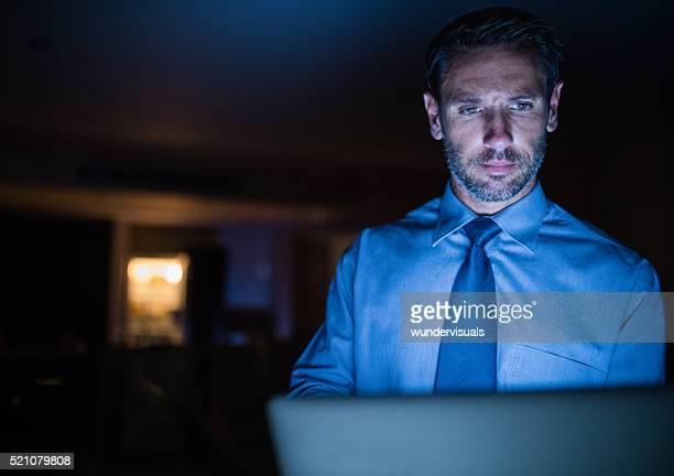Travailler tard dans la nuit homme à l'aide d'un ordinateur portable dans l'obscurité