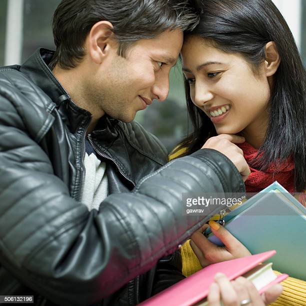 Late teen Asian, student lovers face to face with books.