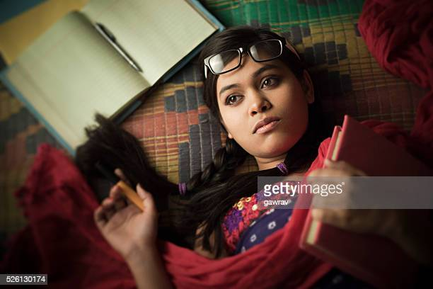 Late teen girl student thinking and reclining on floor mat.