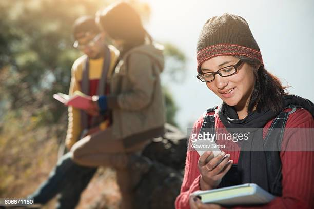 Late teen girl student using smart phone holding a book.