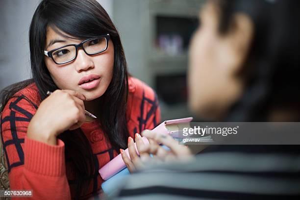 Les Teen fille étudiants avec les livres parler visage à visage.