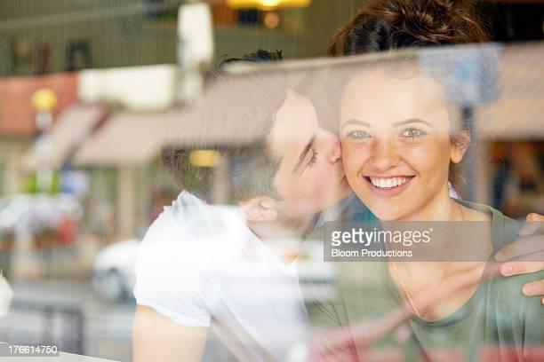 Late teens boy kissing his girlfriend on the cheek