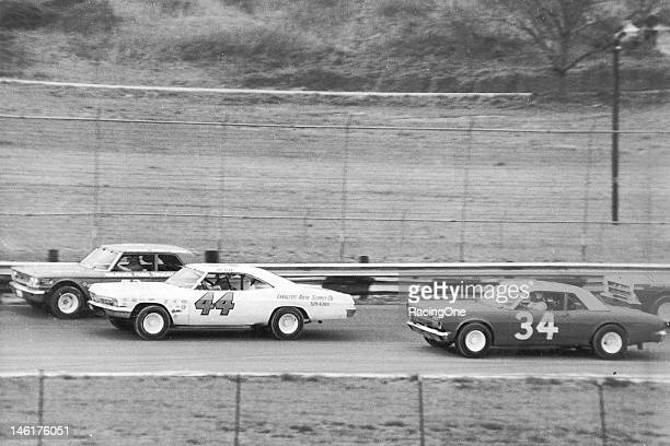 Action during a Late Model stock car race at International Raceway Park has Charlie Perry in a 1963 Ford Galaxie leading the 1966 Chevrolet of Jackie...