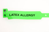 A green latex allergy bracelet isolated on white