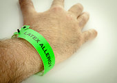 A hand with a green latex allergy bracelet around wrist