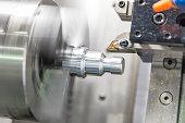 CNC lathe machine (Turning machine)  cutting the aluminium screw thread shaft.Hi-precision CNC machining concept.