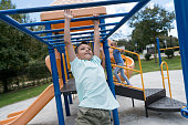 Latin american boy having fun on the monkey bars at the playground looking very happy