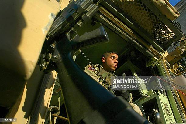 Latin American Soldier Supply Specialist Andre Su from 122 Battalion of the 4th Infantry Division talks on militar radio inside a Bradley fighting...