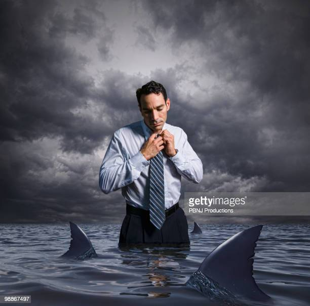 Latin businessman standing in shark infested waters