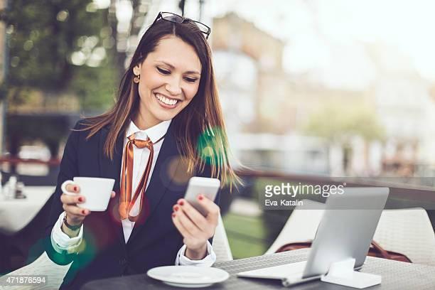 Latin businesswoman text messaging on a smart phone
