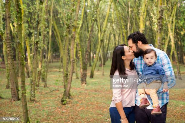 Latin couple kissing and carrying baby boy