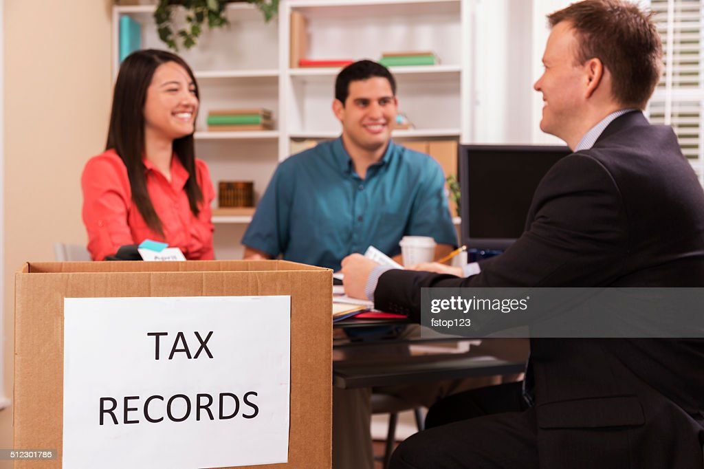 Latin Couple Reviews Income Tax Documents With Accountant. Office. : Stock  Photo