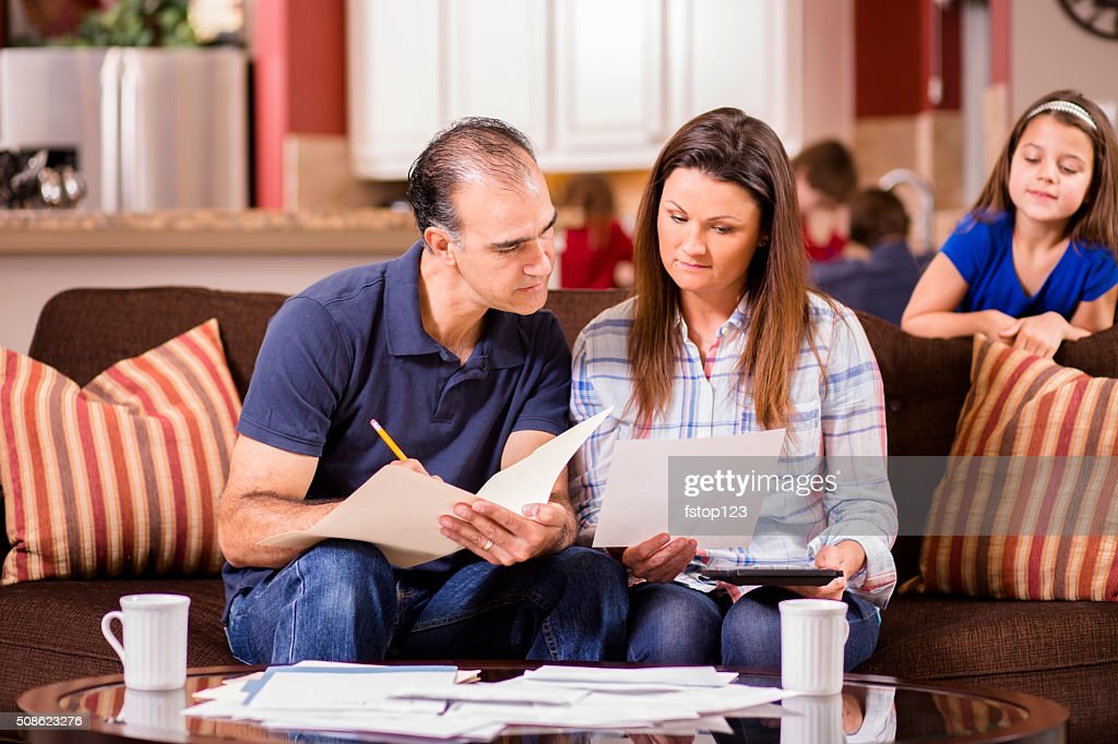 Latin descent couple paying monthly bills at home. : Stock Photo