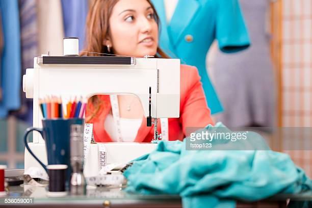 Latin descent seamstress sews fabric, clothing with sewing machine.