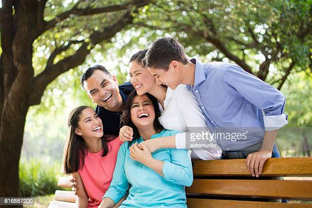 Latin family laughing together outdoors