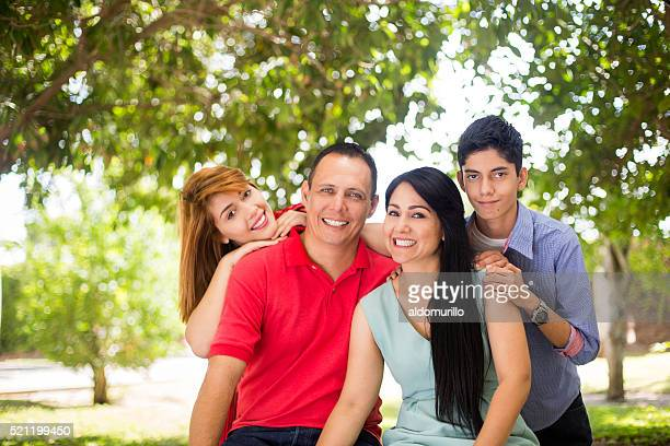Latin family of four looking at camera and smiling