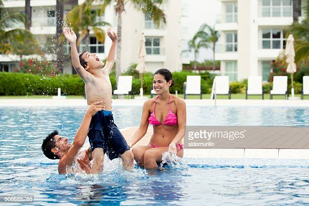 Latin family playing in swimming pool
