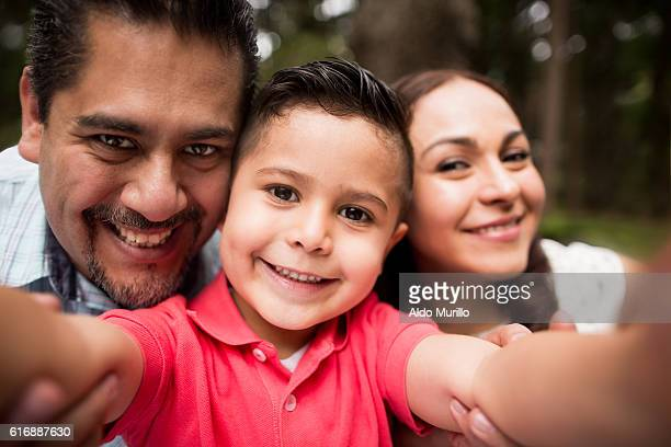 Latin family taking a selfie and smiling at camera