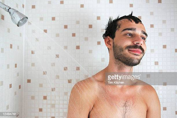 Latin guy in shower, smiling