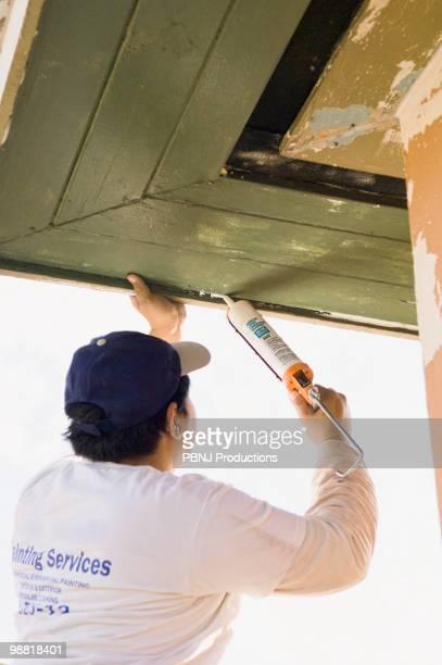 Latin man caulking roof eaves