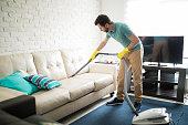 Handsome Hispanic man using a vacuum cleaner to take away the dust in the couch