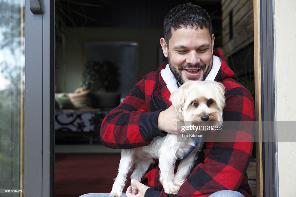Latin man with dog in doorway of country house : Stock Photo