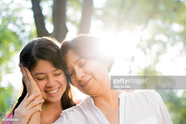 Latin mother holding daughter's head and smiling