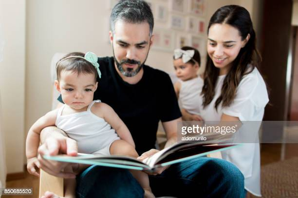Latin mother looking at husband read to baby