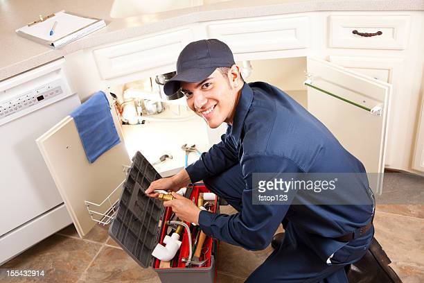 Latin Plumber, repairman working under sink, home kitchen. Service industry.