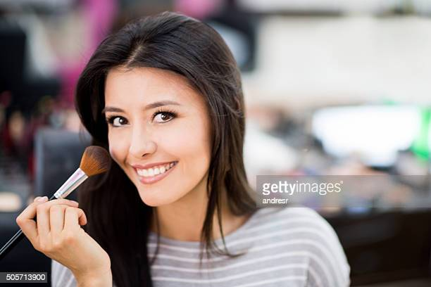 Latin woman applying makeup