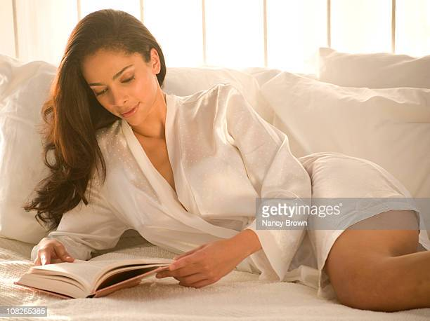Latin woman in bed reading a book.