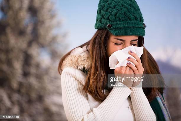 Letra mulher com gripe ou alergia conhecida sneezes enquanto fora. Inverno.