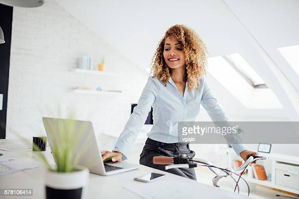 Latina Businesswoman Using Laptop In Her Office.