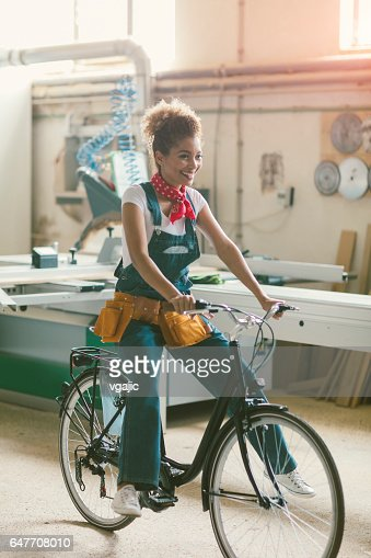 Latina Carpenter on bicycle In Her Workshop : Stock Photo