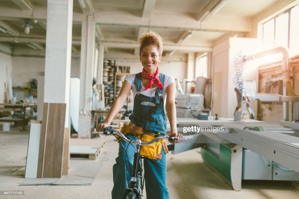 Latina Carpenter riding bicycle In Her Workshop : Stock-Foto