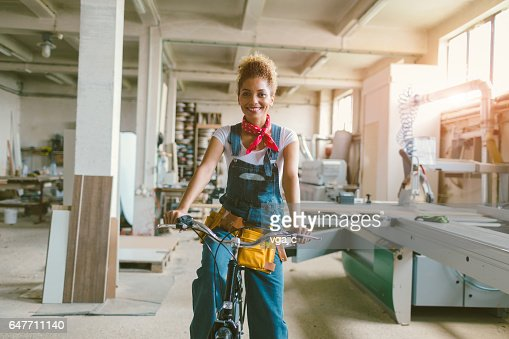Latina Carpenter riding bicycle In Her Workshop : Photo