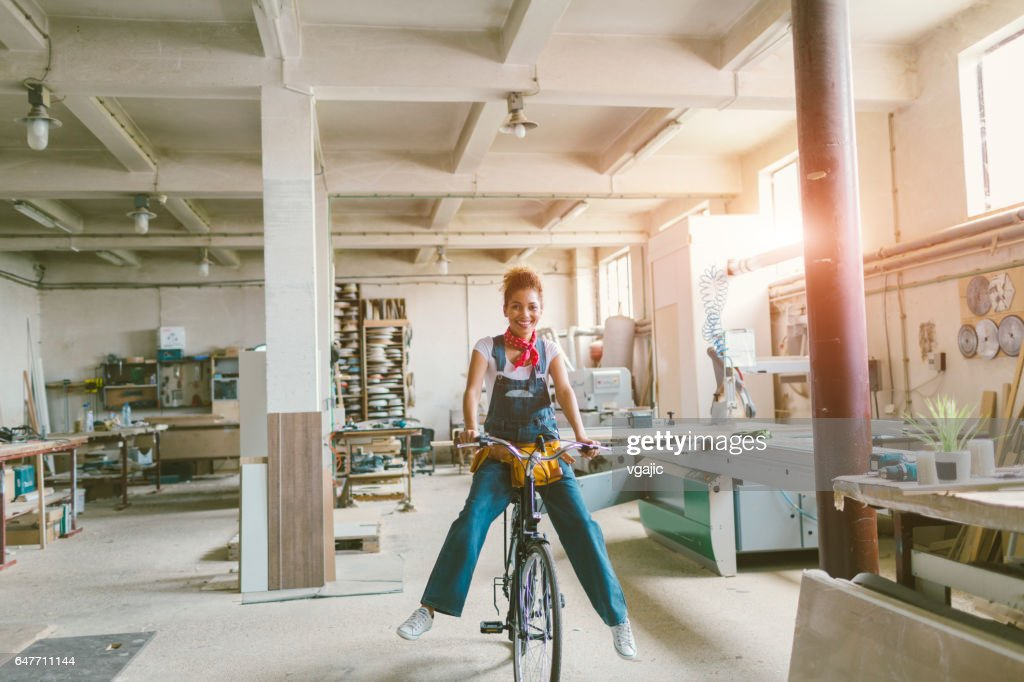Latina Carpenter riding bicycle In Her Workshop : Stock Photo