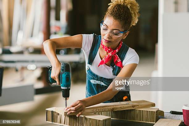 Latina Carpenter mit elektrischer Schraubendreher Im Ihren Workshop