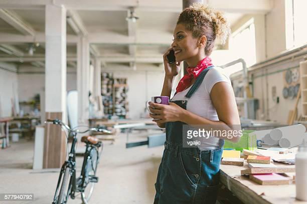 Latina Carpenter Using Phone In Her Workshop