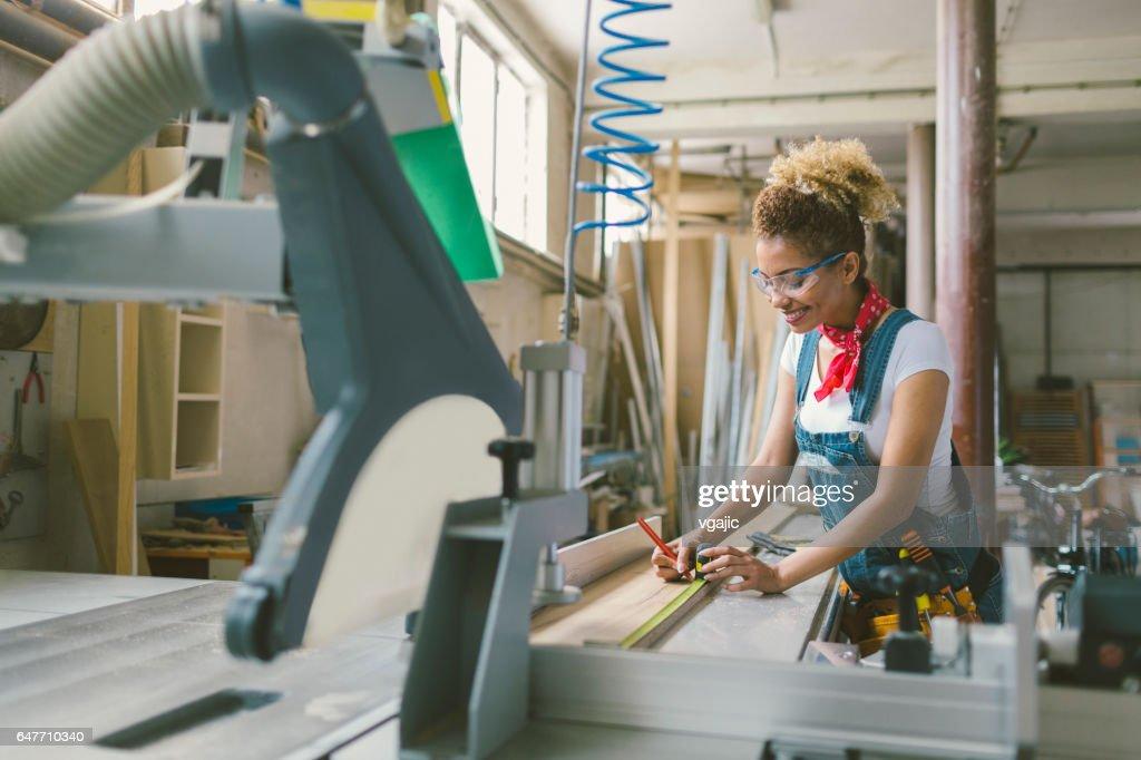 Latina-Zimmermann arbeitet an der Kreissäge : Stock-Foto