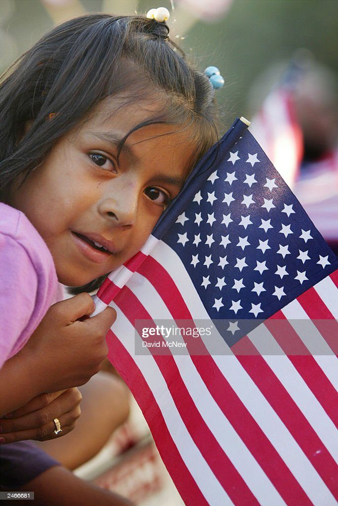 A Latina girl clutches an American flag while waiting to see California Governor Gray Davis sign the controversial SB 60 into law,, allowing undocumented immigrants to get a California driver's license September 5, 2003 in Los Angeles, California. Critics claim that Davis reversed his position on the bill to gain Latino votes in the October 7 recall election.